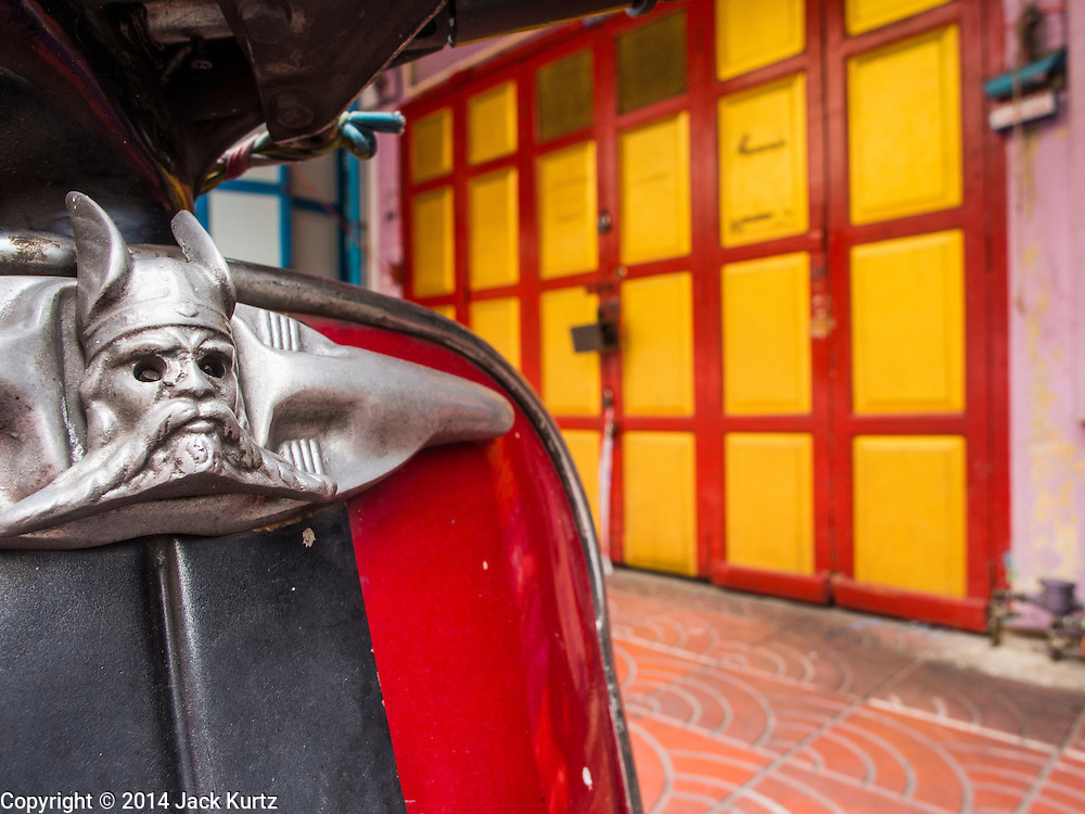 30 AUGUST 2014 - BANGKOK, THAILAND:     A Norse style head on a motorscooter in front of a shophouse in the Chinatown section of Bangkok.    PHOTO BY JACK KURTZ