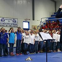 Hamilton music teacher Joanna Pepper leads elementary students in patriotic songs during the school's Veterans Day program Nov. 12.
