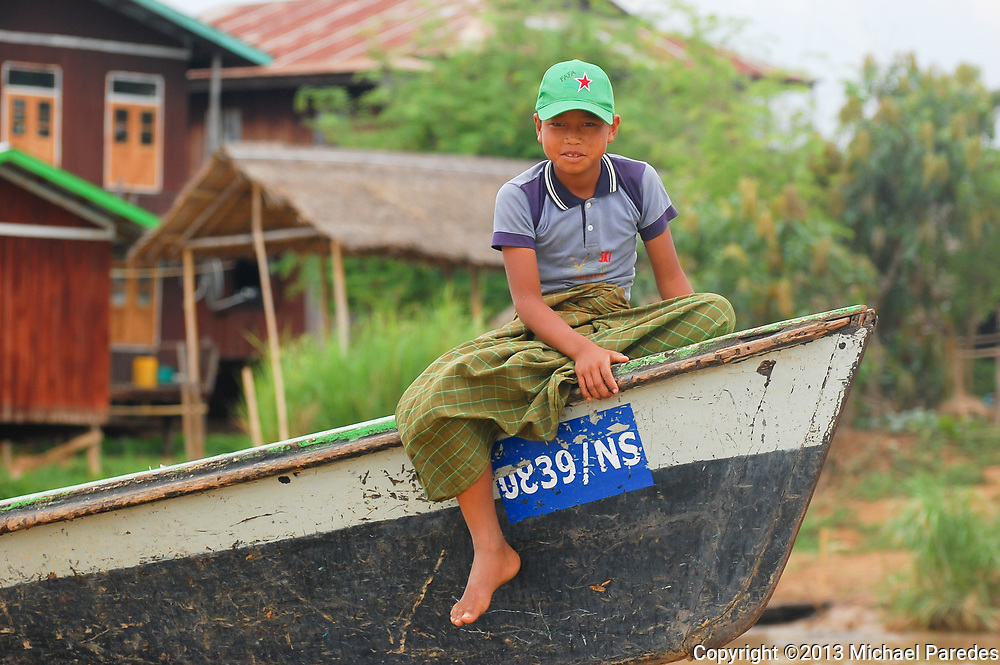 A young boy on Inlé Lake, Burma. He is wearing the typical longyi, which is a long , sarong-type covering