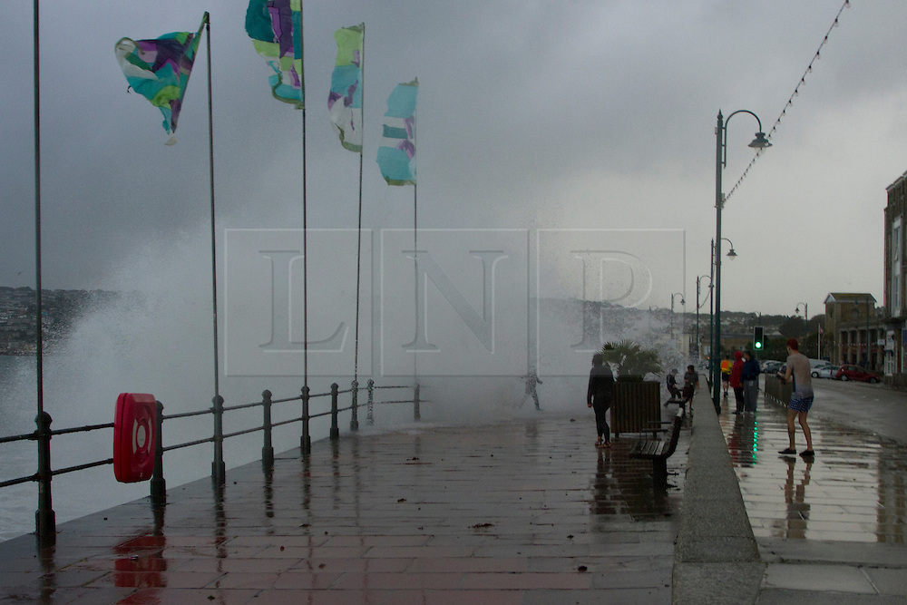 © Licensed to London News Pictures. 15/08/2012. Penzance, UK. A child is caught in a wave crashing over Penzance Promenade. The Police closed the road due to the waves crashing over the road due to high winds but many motorist ignored the warnings. Photo credit : Ashley Hugo/LNP