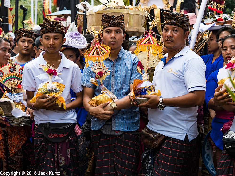 16 JULY 2016 - UBUD, BALI, INDONESIA: Men wait to make an offering during the mass cremation in Ubud. Local people in Ubud exhumed the remains of family members and burned their remains in a mass cremation ceremony Wednesday. Almost 100 people were cremated and laid to rest in the largest mass cremation in Bali in years this week. Most of the people on Bali are Hindus. Traditional cremations in Bali are very expensive, so communities usually hold one mass cremation approximately every five years. The cremation in Ubud concluded Saturday, with a large community ceremony.     PHOTO BY JACK KURTZ