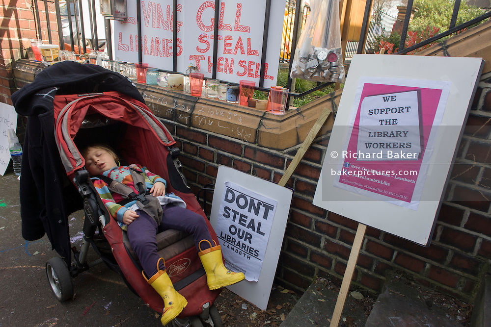 A young protester sleeps outside the now closed Carnegie Library, in Herne Hill, south London on 2nd April 2016. The angry local community in the south London borough have occupied their important resource for learning and social hub for the weekend. After a long campaign by locals, Lambeth have gone ahead and closed the library's doors for the last time because they say, cuts to their budget mean millions must be saved. A gym will replace the working library and while some of the 20,000 books on shelves will remain, no librarians will be present to administer it. London borough's budget cuts mean four of its 10 libraries will either close, move or be run by volunteers. (Photo by Richard Baker / In Pictures via Getty Images).
