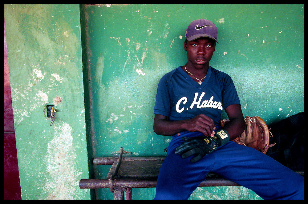 In his first year in the elite Cuban baseball system, Juan Carlos Torriente, 15, relaxes in the dugout before a scrimmage at the Centro Deportivo Jose Martí in Havana. Torriente was competing for a place on the Cuban National junior team.