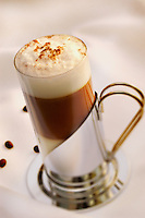Capuccino on white tablecloth with coffe grains