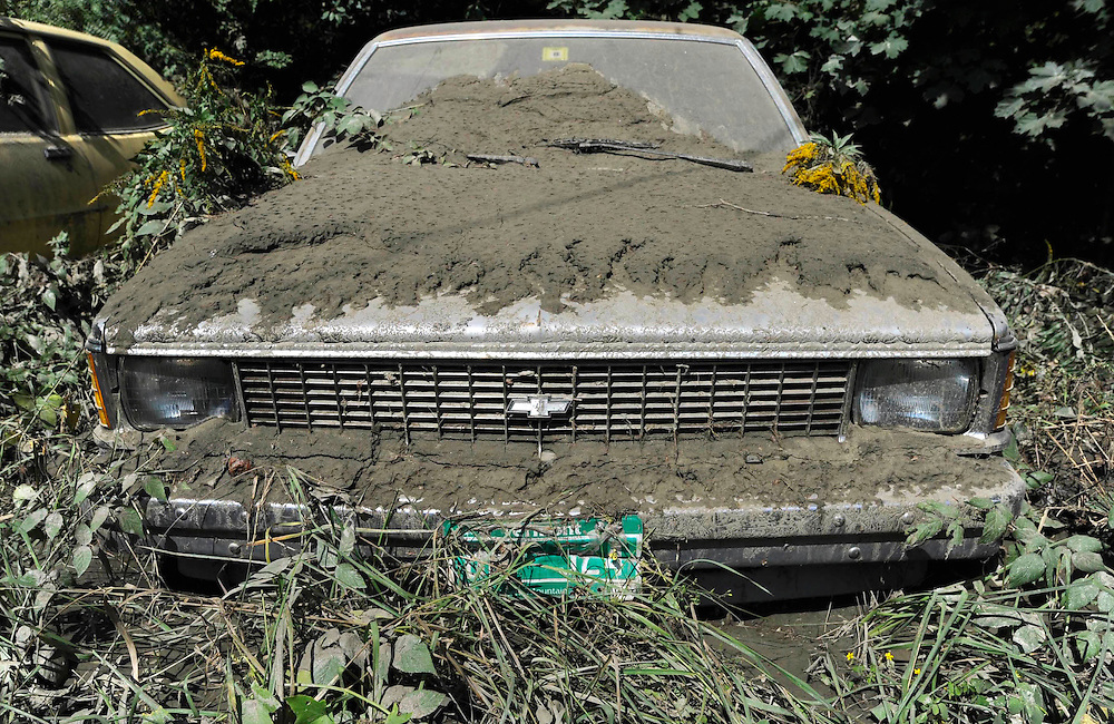 A parked car is seen covered in mud along Route 9 in the aftermath of Tropical Storm Irene, in Brattleboro, Vt., Tuesday, Aug. 30, 2011.  (AP Photo/Jessica Hill)