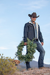 cowboy with a Christmas wreath on a mountain top