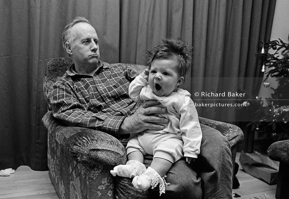'Christmas Comes but once a Year ..'  A grandfather holds his tired granddaughter at arms-length while watching a television prgramme at Christmas time. The baby girl is 5 months-old and yawns with a wide, open mouth while the elder relative pouts, looking grumpy. Both are seated on an armchair in the family home's living room. A decorated Christmas tree is seen in the far corner and the curtains behind are drawn. This is from a documentary series of pictures about the first year of the photographer's first child Ella. Accompanied by personal reflections and references from various nursery rhymes, this work describes his wife Lynda's journey from expectant to actual motherhood and for Ella - from new-born to one year-old.