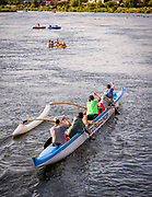 Outrigger crew paddles on the Deschutes River next to the Old Mill District in Bend, OR
