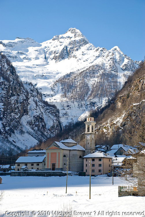 Ticino, Southern Switzerland. Valle Verzasca, Sonogno.  Pretty italianate church in the foreground with the magnificent snowy alps towering above. Vertical.