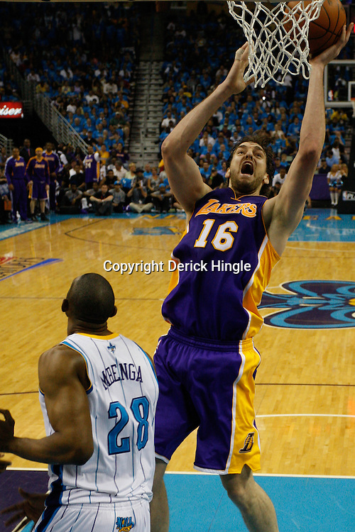 April 28, 2011; New Orleans, LA, USA; Los Angeles Lakers power forward Pau Gasol (16) shoots over New Orleans Hornets center D.J. Mbenga (28) during the third quarter in game six of the first round of the 2011 NBA playoffs at the New Orleans Arena. The Lakers defeated the Hornets 98-80 to advance to the second round of the playoffs.   Mandatory Credit: Derick E. Hingle