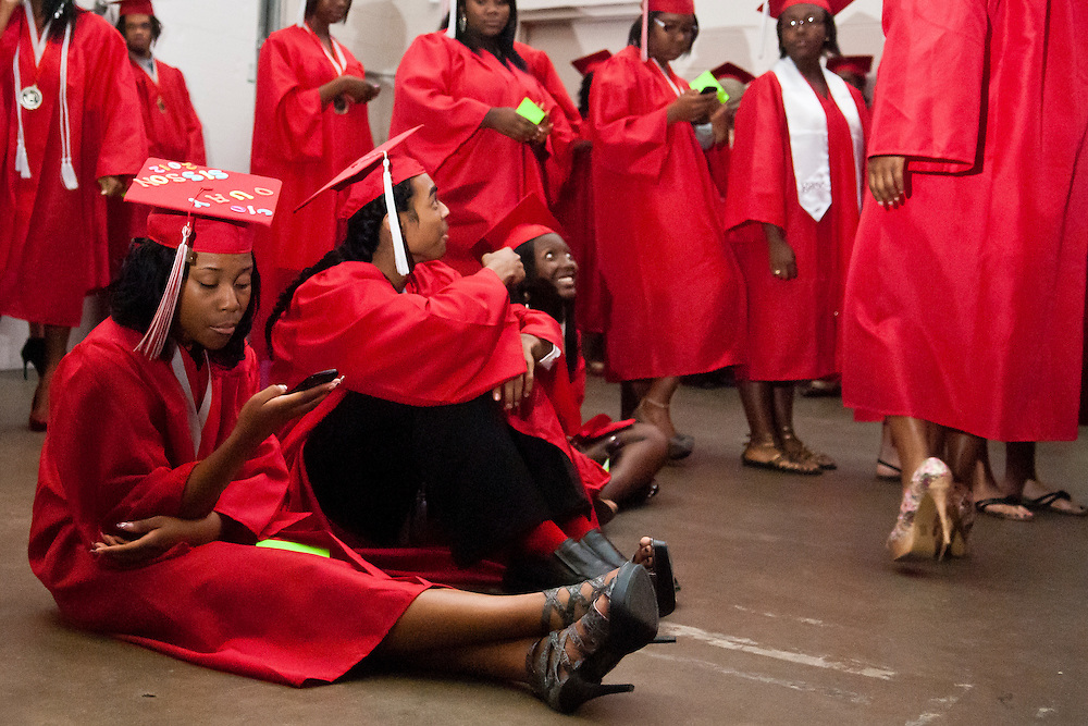 Lathan Goumas | MLive.com..Northern High School graduate Chinquay Sisson, 17, sits on the floor and uses her phone to pass time before the 2012 Flint Community Schools commencement ceremony at the Perani Arena in Flint, Mich. on Tuesday June 5, 2012.