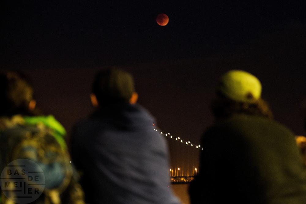 Mensen kijken naar de maansverduistering op de pier. In San Francisco is de supermaansverduistering goed te zien boven de Bay Bridge. Veel mensen komen op het verschijnsel af. Niet alleen is de maan volledig verduisterd, het is ook nog eens een zogenaamde supermaan omdat die dicht bij de aarde staat. De eerstvolgende supermaansverduistering vindt pas op 8 oktober 2033 plaats.<br /> <br /> San Francisco the super lunar eclipse is clearly visible above the Bay Bridge. Many people come to see the phenomenon. Not only is the moon obscured, it is also a so-called super moon because it is close to the earth. The next super lunar eclipse will only take place on October 8, 2033.