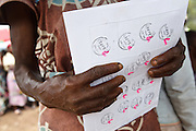 A woman holds a sheet of coupons she's received during a non-food item fair at the Miketo IDP settlement, Katanga province, Democratic Republic of Congo on Sunday February 19, 2012. Displaced people who have lost most of their belongings as they fleed their homes receive coupons their can exchange for goods at a fair held in partnership with local traders.