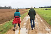 Man and woman walking in countryside winter, Ramsholt, Suffolk, England, UK