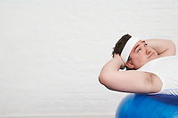 Overweight Man doing sit-ups on Exercise Ball