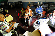 A young women with her two children listen to doctors and consultants from the 'Nefrolempa' health project, explain the results of their medical tests into the high incidence of chronic renal failure in the region.<br /> <br /> Community of Nueva Esperanza, Bajo Lempa, El Salvador. 2011.<br /> The 'Nefrolempa' research project is a collaboration between the El Salvador Ministry of Health, the Nephrology Institute of Cuba's Ministry for Public Health and the United Bajo Lempa Committee Association. The aim of the project is to investigate the reasons for the high levels of Chronic Kidney Disease (CKD) suffered by the communities within the Bajo Lempa region. It is exploring whether the use of agrochemicals might be a factor in the prevalence of the disease.