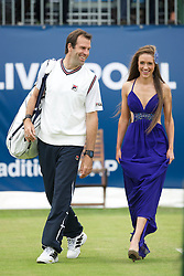 LIVERPOOL, ENGLAND - Friday, June 17, 2011: Greg Rusedski (GBR) walks on court with a model wearing clothes from the Dressing Room during day two of the Liverpool International Tennis Tournament at Calderstones Park. (Pic by David Rawcliffe/Propaganda)