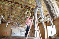 Young woman climbing up the ladder while looking at ceiling