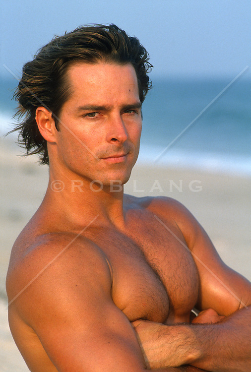 Shirtless man with his arms crossed at the beach