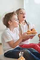 Siblings blowing candles on cupcakes