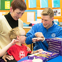 St Johnstone players visit Fairview School in Perth.....19.12.13<br /> David Wotherspoon hands out a selection box to Alfie Ashcot who is pictured with teacher Barbara Dunlop who then proceeded to teach David Wotherspoon how to sign Merry Christmas to Alfie.<br /> Picture by Graeme Hart.<br /> Copyright Perthshire Picture Agency<br /> Tel: 01738 623350  Mobile: 07990 594431