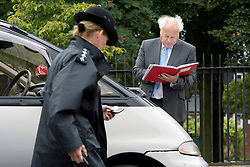 © London News Pictures. 19/09/2013. London, UK. Judge Keith Cutler (right) examines notes next to a car used as a replica for the car Mark Duggan was travelling in at the scene where Mark Duggan was shot dead by armed police in an incident that sparked the 2011 London Riots. Judge Cutler and The family of Mark Duggan attended a visit by the Jury to the scene of the incident as part of an ongoing inquest into the death of Mark Duggan. Photo credit: Ben Cawthra/LNP
