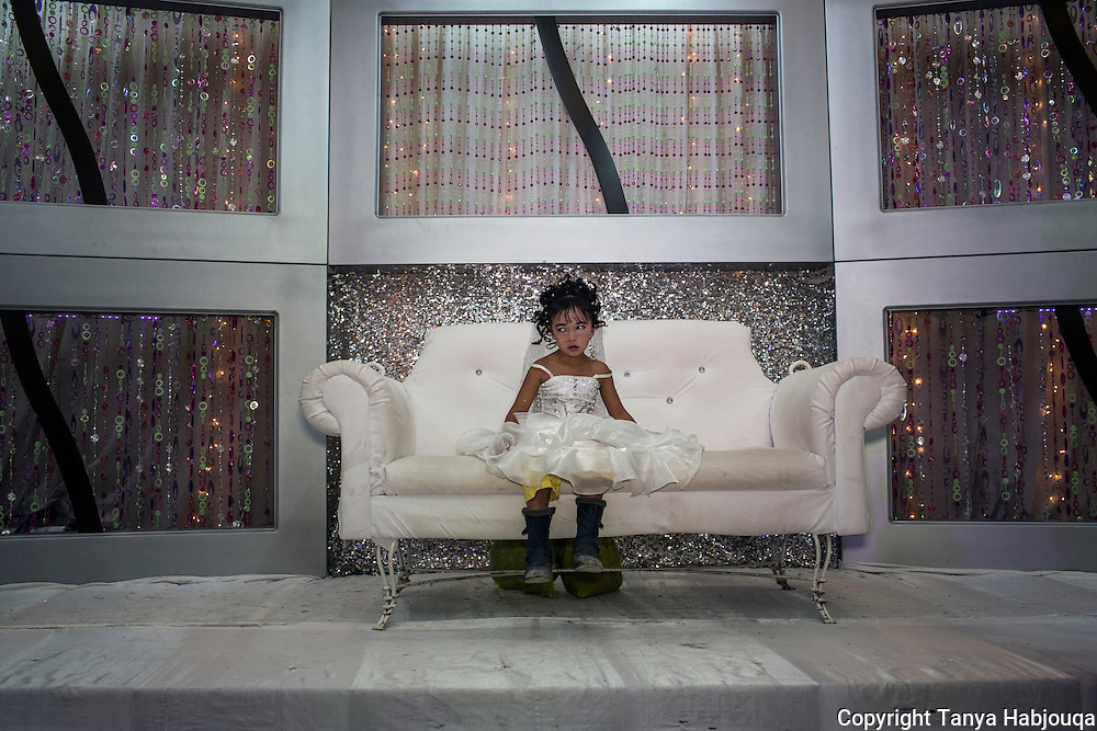 Summer is the most popular time for weddings in Gaza, usually celebrated in a wedding hall. Here, the niece of the bride perches on the popular bride and groom love couch.