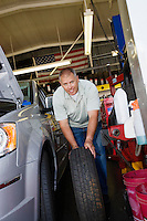 Auto Mechanic Changing a Tire