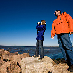 A young couple watches for wildlife on a rock breakwater at Long Beach in Stratford, Connecticut.  Adjacent to the Great Meadows Unit of McKinney National Wildlife Refuge.