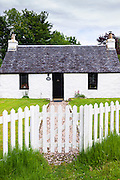 Quaint traditional highland stone bungalow cottage with white paling fence at Port Appin, Argyllshire in the Highlands of Scotland