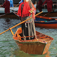 """VENICE, ITALY - JANUARY 06:  One of the rowers dressed in costume sails on the Grand Canal at the end of the """"Befana"""" Regatta on January 6, 2014 in Venice, Italy. In Italian folklore, Befana is an old woman who delivers gifts to children throughout Italy on the feast of the Epiphany on January 6 in a similar way to Saint Nicholas or Santa Claus.  (Photo by Marco Secchi/Getty Images)"""