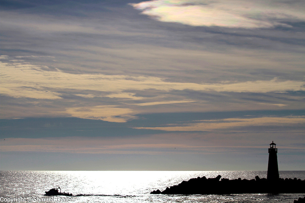 Afternoon clouds streak an other-worldly skyscape over the jetty as a boat head out of the Santa Cruz Small Craft Harbor on January 10.