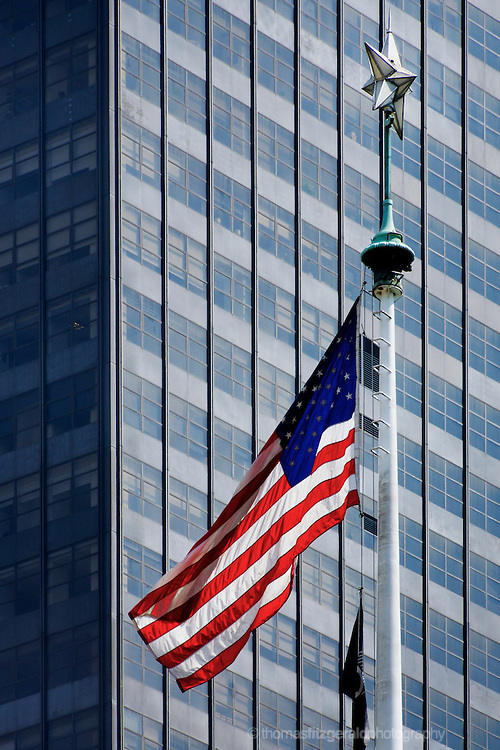 A US Flag blows in the wind in front of the glass windows of a Skyscraper behind it