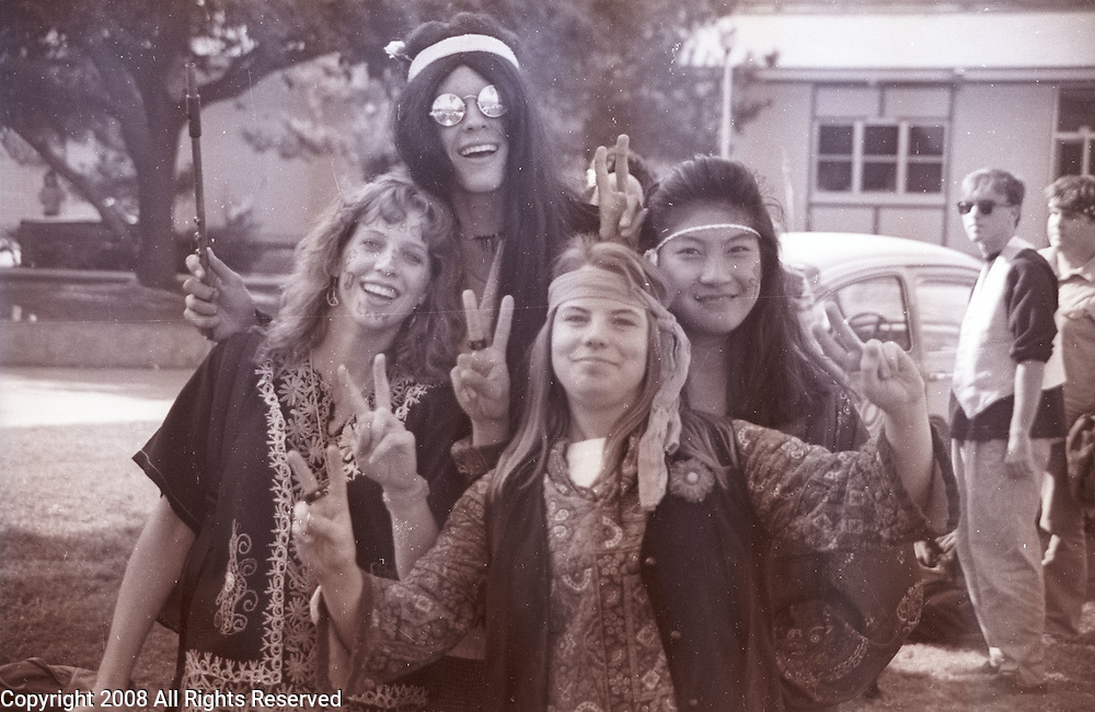 A group of high school friends flash peace signs while dressed as hippies during homecoming week activities in the central valley town Porterville, California in 1989.