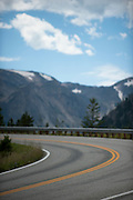 A mountain road curves to the left with snowcapped mountains in the background. Missoula Photographer, Missoula Photographers, Montana Pictures, Montana Photos, Photos of Montana