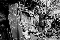 "58 year old Catholic Croat. Praying outside his bombed out home, Ostrovo, Croatia. He's describes his place ""as not fit for a dog to live in"" 1998"