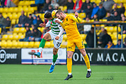 Mohamed Elyounoussi (#27) of Celtic FC and Nicky Devlin (#2) of Livingston FC contest a header during the Ladbrokes Scottish Premiership match between Livingston FC and Celtic FC at The Tony Macaroni Arena, Livingston, Scotland on 6 October 2019.
