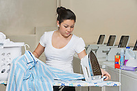 Young female employee ironing clothes in Laundromat