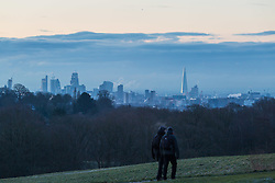 "Two walkers cross Hampstead Heath, with London's skyline in the distance. The threatened snow from ""The Beast From The East"" weather system doesn't materialise overnight in London leaving a crisp, clear morning, seen from Hampstead Heath in North London. London, February 27 2018."