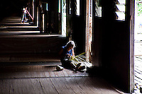 Old woman weaving a basket in the communal balcony area of the Murat Longhouse as another resident sweeps in the distant background.