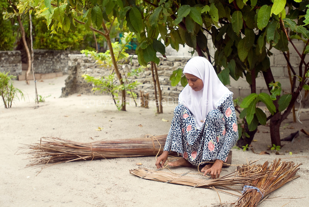 The island of Utheem. North Maldives. Woman weaving coconut palm thatch.