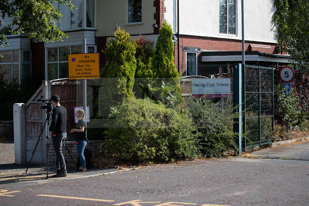 """© Licensed to London News Pictures. 19/07/2018. Salford, UK. Documentary TV crew by the school gates . Harrop Fold School in Little Hulton is closed for a protest by parents , objecting to the outcome of a months-long investigation in to record keeping which, it is alleged, revealed that data relating to pupils' performance was embellished and which has seen the school's popular headmaster suspended from duty. Parents planned a protest following the suspension of head master Drew Povey alongside three other members of staff . The school , which has been featured in the documentary """" Educating Greater Manchester """" will remain closed throughout the day . Photo credit: Joel Goodman/LNP"""