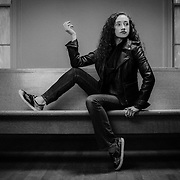 A 16-year-old teenage girl wearing a black leather jacket and jeans sits on a pew bench in a 19th Century church in Pittsboro, NC.