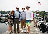 Maria Young, Tom O'Brien, Mike Welsch and Ralph Brooks on the dock at Winnipsquam Marine as they prepare for Welch's swim of Lake Winnisquam on Saturday morning.  (Karen Bobotas/for the Laconia Daily Sun)