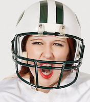 Portrait of young woman in football uniform screaming against gray background