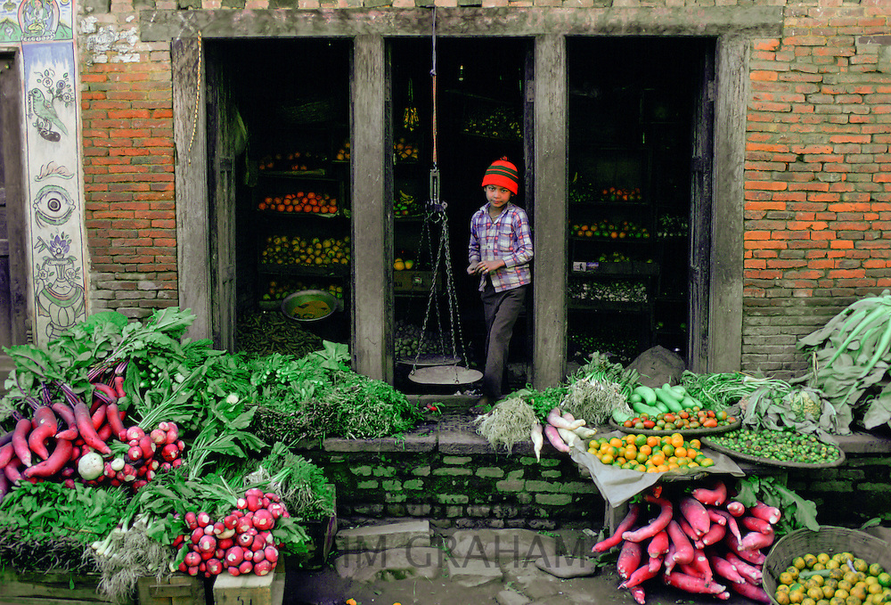 A young boy in a checked shirt and red knitted hat  in the doorway of a fruit and vegetable shop in Patan, Nepal