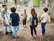 30 JULY 2016 - BANGKOK, THAILAND:  A man (center, facing camera) who lives in the Pom Mahakan Fort talks to Thai tourists who visited the community before it is razed by city officials. Residents of the slum have been told they must leave the fort and that their community will be torn down. Mahakan Fort was built in 1783 during the reign of Siamese King Rama I. It was one of 14 fortresses designed to protect Bangkok from foreign invaders. Only of two are remaining, the others have been torn down. A community developed in the fort when people started building houses and moving into it during the reign of King Rama V (1868-1910). The land was expropriated by Bangkok city government in 1992, but the people living in the fort refused to move. In 2004 courts ruled against the residents and said the city could take the land. Eviction notices have been posted in the community and people given until April 30 to leave, but most residents have refused to move. Residents think Bangkok city officials will start evictions around August 15, but there has not been any official word from the city.     PHOTO BY JACK KURTZ
