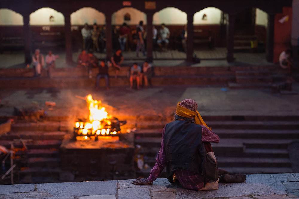 A hindu saint watching the proceedings of cremation at the ghats of Pashupathinath Temple.<br />