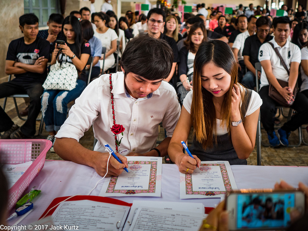 "14 FEBRUARY 2017 - BANGKOK, THAILAND:  A couple signs their wedding registration while other while other couples wait to get married in the Bang Rak district in Bangkok. Bang Rak is a popular neighborhood for weddings in Bangkok because it translates as ""Village of Love."" (Bang translates as village, Rak translates as love.) Hundreds of couples get married in the district on Valentine's Day, which, despite its Catholic origins, is widely celebrated in Thailand.     PHOTO BY JACK KURTZ"