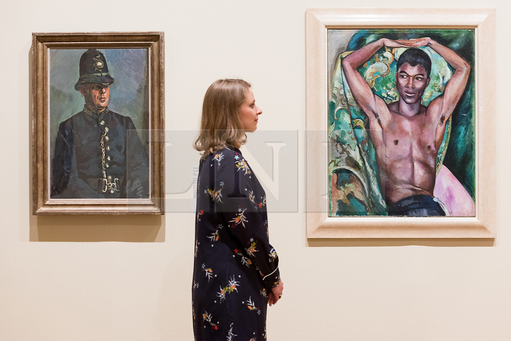 © Licensed to London News Pictures. 03/04/2017. (L to R) Museum staff views a painting titled PC Harry Daley by artist Duncan Grant and a portrait of Pat Nelson by artist Edward Wolfe showing as part of Tate Britain's Queer British Art exhibition. London, UK. Photo credit: Ray Tang/LNP
